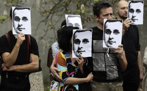 Petr David Josek/AP/TT Fängelsedomen mot Oleg Sentsov har mött skarp internationell kritik. Här demonstrerar människor utanför Rysslands ambassad i Prag förra året genom att hålla upp ett porträtt av Sentsov. Arkivbild.
