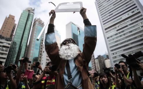 Jae C Hong/AP/TT En demonstrant utklädd till Moses håller upp en stentavla vid en protest i Hongkong.