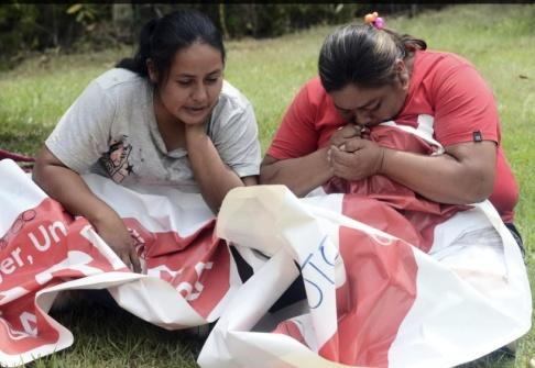 El País/AP/TT Anhöriga till Karina García sörjer, med hennes valmaterial i famnen, efter beskedet om mordet.