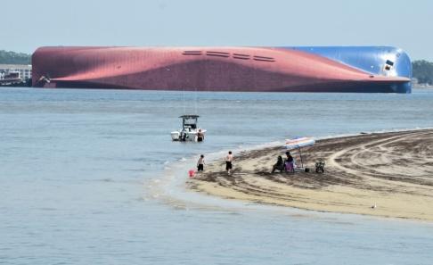 Terry Dickson/AP/TT Människor på Jekyll Island ser på det kapsejsade fraktfartyget.