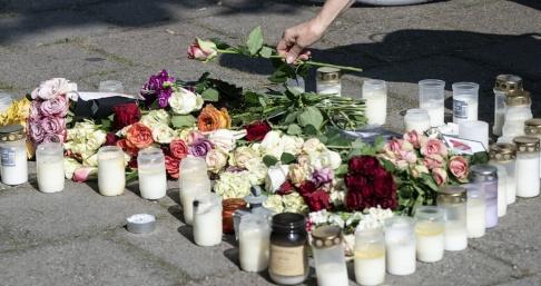 Johan Nilsson/TT En kvinna lägger ner en ros vid minnesplatsen på Sergels väg i stadsdelen Ribersborg i Malmö där 30-åriga Carolin Hakim sköts till döds den 26 augusti. Arkivbild.