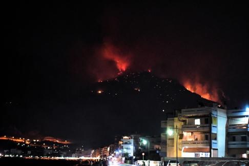 Upplysta byggnader framför ett brinnande berg under en skogsbrand cirka 80 km väster om Aten i Grekland. Bilden är från igår den  14 september 2019. EPA / VASSILIS PSOMAS