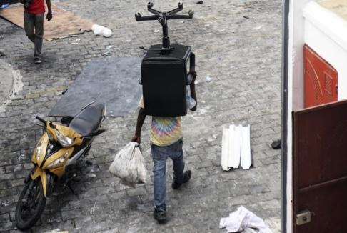 Edris Fortune/AP/TT En man i Port-au-Prince bär iväg på en stol under plundringarna av butiker i staden.
