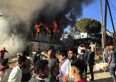 InTime News via AP/TT En container som utgjort en bostad brinner i lägret i Moria på ön Lesbos.