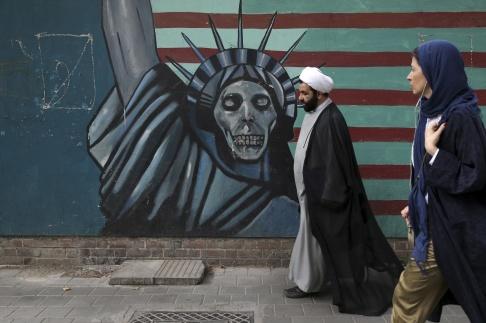 Vahid Salemi/AP/TT Frihetsgudinnan med skelettansikte står framför en flagga som utanför bild övergår i taggtråd som omger den iranska kartbilden. Arkivbild.
