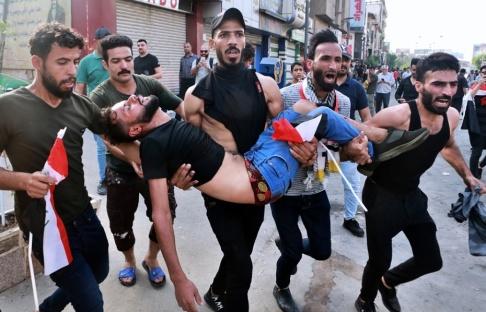 Khalid Mohammed/AP/TT Hundratals människor i Bagdad och i södra Irak protesterade mot bland annat korruption under tisdagen. Här bärs en skadad demonstrant bort.