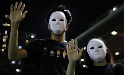 Kin Cheung/AP/TT Maskerade demonstranter håller upp sina fingrar, vilket syftar på fem krav de har för att sluta protestera.
