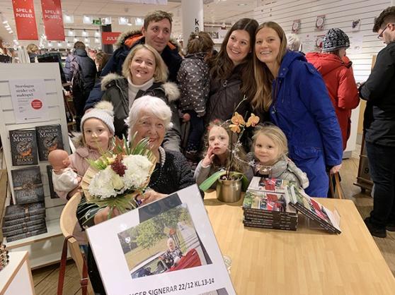 Inger Grimlund signerar böcker på Akademibokhandeln i julas. Runt henne har barn, barnbarn, och barnbarnsbarn samlats.