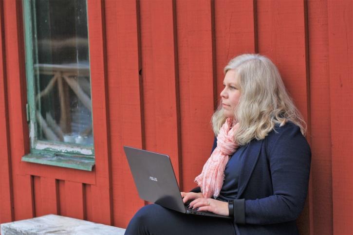 Bilden föreställer Charlotta Hurtig som sitter med en laptop i knät utanför ett falurött hus. Charlotta är digital kommunikation på CH Digitalbyrå.
