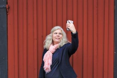 Bilden föreställer Charlotta Hurtig, digital kommunikatör på CH Digitalbyrå, som tar en selfie mot en faluröd vägg.
