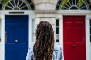 En tjej står framför en blå och en röd dör. Vilken ska hon välja. Vilkan digital kanal ska du välja för ditt företag?