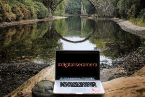 En laptop står på en klippa vid en flod. Vatten, gröna träd. Texten #digitaliseramera på laptopen. Digitalisera din kunskap men hjälp av onlinekurser.
