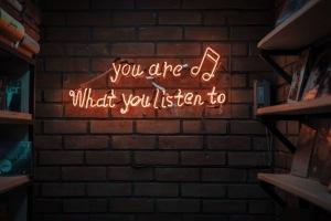 Text i neon: You are what you listen to. Läs om mina favoritpoddar inom digital marknadsföring.