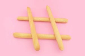 En hashtag gjord av brödpinnar mot rosa bakgrund. Läs mer om Instagram i blogginlägget.