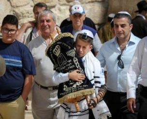 En judisk pojke vid Västra muren i Jerusalem bär en bokrulle. Foto: Mikael Kurkiala/Ikon