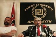 Nynazistledaren Nikos Michalolioakos framför partiets emblem, hämtat från tiden 1936-41. Den nazistiska benämning Golden Dawn har brittiskt ursprung.