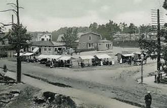 """Sundbybergs Torg 1902. Stationsgatsbacken rinner ner över järnvägen och möter Landsvägen. På torget finns stånd och basarer. Frälsningsarmén har varit på nuvarande plats i hörnet Torget 3/Bangatan 1 sedan , ja, enl insändaren Icke-Mulle måste det ha varit sen 1896 i alla fall. Det är huset längst bort på torget med ett litet hus framför, Finkan eller """"Hotellet"""" kallad. Landsvägen blev som första gata stensatt 1914. Bild från Museet."""