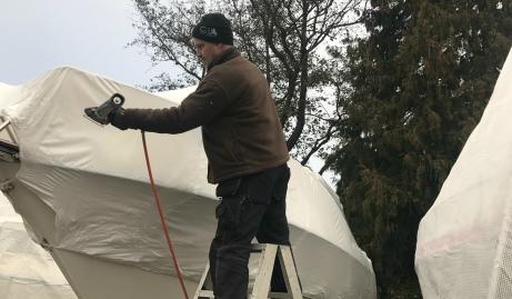 Göran Jämtin värmer plastklädseln med en värmeblåsare så att den smiter tight kring båten.