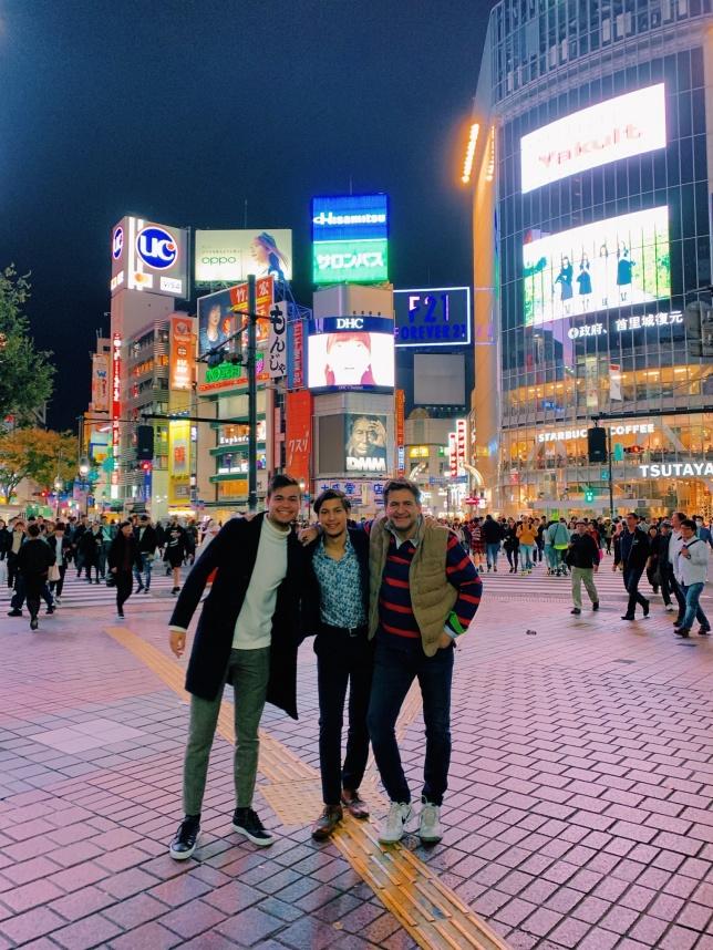 Fr v Bröderna Douglas och James samt pappa Håkan  snackar kvällens nöjesstrategi. Bakom dem ligger världens största övergångsställe, Shibuya Crossing.