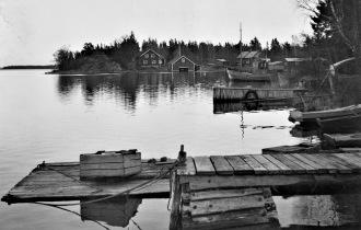 Från Sikviks fiskeläge. Tv från front: Södermans brygga, Larssons brygga och de två husen längst bort är ett båthus och ett vanligt hus tillhörande fiskare Wallström. Th Albin och Enok Söderman som tjärar ryssjor i ett kar. Fiskebåten är upphängd i båthuset. I Sikvik fanns också fiskarefamiljen Östman. Bilderna från Gävle Stadsarkiv.