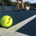 Tennisboll (i fokus) på bana m underdelen på människa i bakgrund