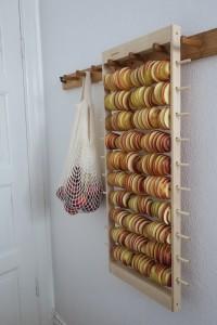 Apelstapeln äppeltork hänger på en vägg på en knoppbräda