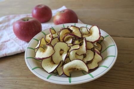 En skål med torkade äppelringar på ett bord med äpplen