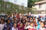 Glädje på skolgården, med resenärerna i bakgrunden.