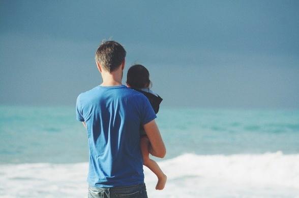 Pappa och barn blickar ut över havet tillsammans