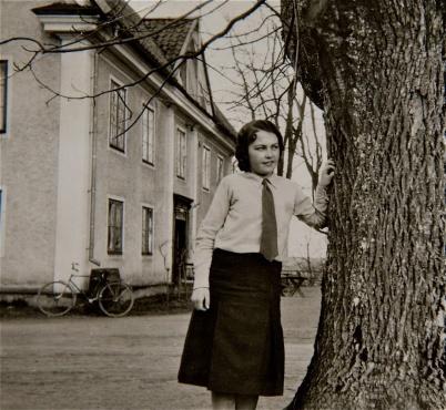 Wera Johansson poserandes vi ett av de träd som ingick i den gamla allén vid Lindö gård. Bilden troligtvis tagen någon gång på 1940-talet. Fotograf okänd.