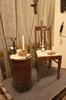 Litet bord av gammal brandspruta, stol och små ljusstakar