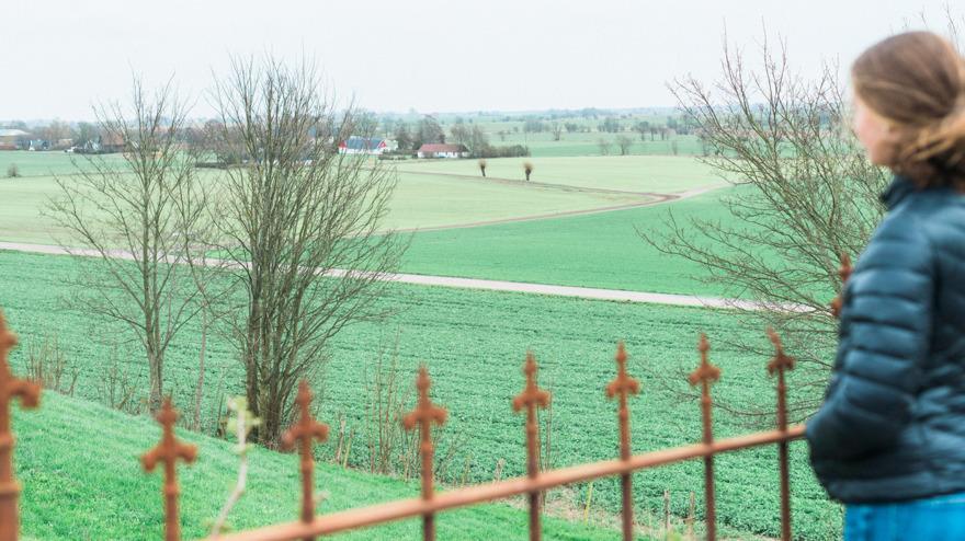 Min praoelev Tilde blickar ut över landskapet. Nu är det april. Tänk er utslagna träd och böljande fält i sommar.