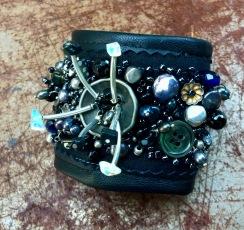 Armband; Svarat änkan. Silver, pärlbroderi, onyx, agat, månsten, sötv.pärlor och gamla knappar på svart linnetyg och svart skinn.