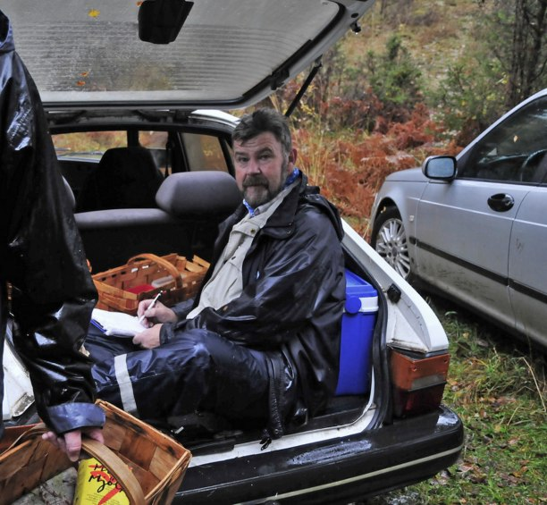 Ordförande Johansson var tvungen att ta skydd för regnet för att kunna skriva artlista och vad var då lämpligare än att hoppa upp i bagageluckan på bilen!