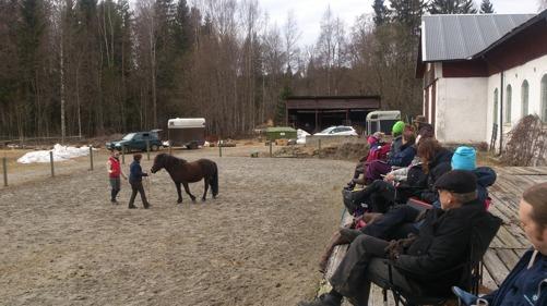 Karin och Ör instrueras av Angelica. Frusna men påpälsade åhörare lyssnar och iaktar nogsamt. :)