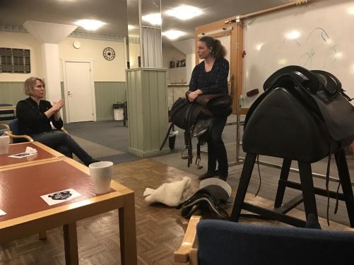 Pia svara på frågor och visar samtigit på en sadel