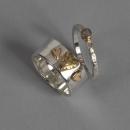 silver ring med guldhjärtan och en tunnare ring med guldinfattad rådiamant