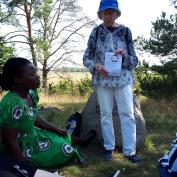 Vimbai lyssnar på Berit Åhlander, som berättar om frälsarkransen vid Gamla Uppsala församlings meditationsplats.