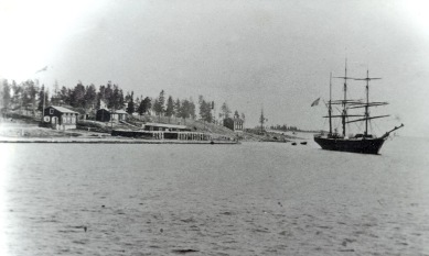 1890-talsbild från Karlsborg. Lotsstugan längst till vänster, sedan har vi stugan med O. Johanssons fotoatelje och längst ut skeppshandlare P.G. Schmaltz affär. Fotot taget av O. H. Bergström. Ur B-G Nilssons bildsamling.
