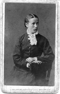 Bilden visar Maria Johansdotter, född 2/5 1860 i Korpikån. Johan Fredrik Nilsson och Greta Cajsa Carlsdotter hette föräldrarna. De var bönder på hemman nr 1 i Korpikå.   På bilden ser man att vänstra handen saknar ringar. Det skulle betyda att fotot är taget före 1884 då hon gifte sig med Johan Fredrik Emmoth, kanske är det taget på hennes 20-årsdag? De bosatte sig på Innanbäcken där de 1890 köpte en hemmansdel av nr 4 i Lappkullen. Innan arrenderade de hemmanet Landet i Rolfs ett par år. Hon dog på Innanbäcken den 3 juni 1938. Loggan är utan röd kant och hemvisten är Nederkalix.