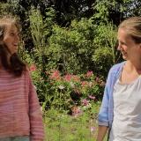 två flickor som skrattar, tröja i rosenrosa 908, kofta i himmelsblå 906