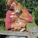 en flicka med katt, kofta i barkbrun 909, mössa i sommargul 982