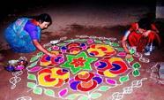 Kvinnor målar kolam-rangoli.