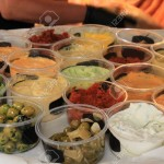 91201426-various-spanish-tapas-in-small-plastic-containers-on-a-market-stall-olives-garlic-sauce-and-various-