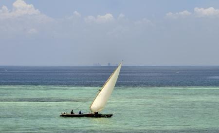 en fiskebåt, man kan skymta  Dar es Salaams skyskrapor i bakgrunden...