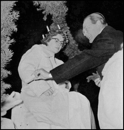 Kyrkoherde Harald Ängquist delar ut presenter till Töcksmarks Lucia Gunilla Ringsby med tärnor, på lastbilsflaket i Töcksfors centrum före avfärd till kyrkan, 1950-talet.