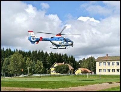 Polishelikoptern lyfter från fotbollsplanen vid Töcksfors skola, för att delta i rånarjakten.