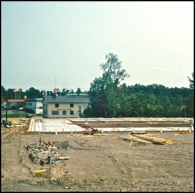 Texaco bensinstation och bilverkstad  är borta och bottenplattan till Kötthallen är snart klar. I bakgrunden syns Töcksfors Elektriska och Lågprisvaruhuset Gränslöst.