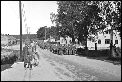 Militärer marscherar genom Töcksfors i början av 1940-talet, under andra världskriget.
