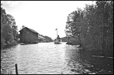 Ångbåten IDUN passerar i farleden vid Töcksfors sågverk på väg till hamnen vid Bruket i slutet av 1930-talet.